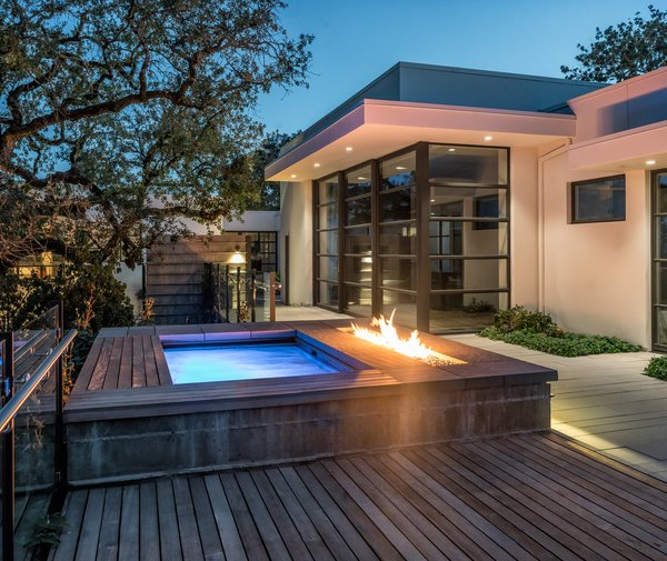 Modern home with outdoor, wood patio, porch, deck, small pool, concrete patio, porch, deck, trees, shrubs, small patio, porch, deck, hardscapes, back yard, and landscape lighting. Lighted spa and fire feature at twilight Photo 7 of Hilltop Haven