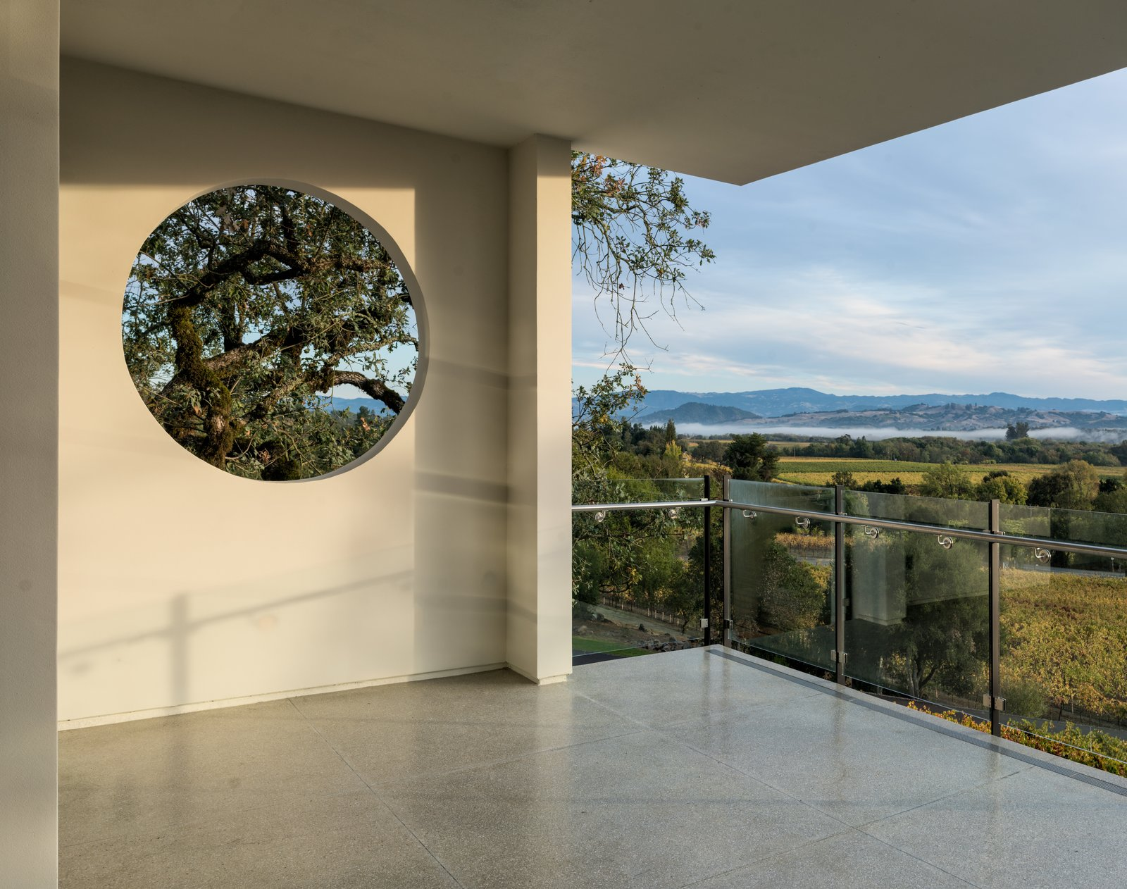 Framed views of the surrounding landscape from main floor level Tagged: Outdoor, Trees, Hardscapes, and Concrete Patio, Porch, Deck.  Hilltop Haven by Randy Thueme Design