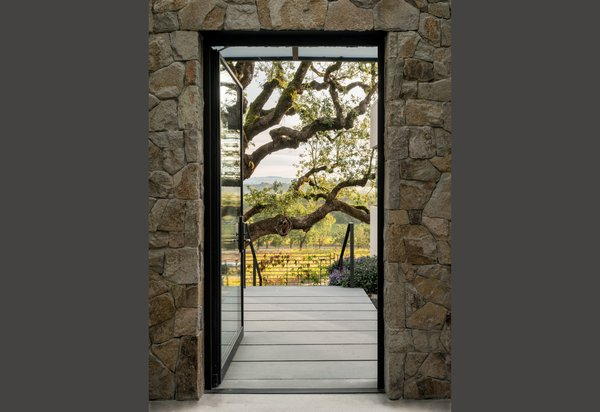 Modern home with outdoor, trees, shrubs, gardens, front yard, hardscapes, stone patio, porch, deck, and concrete patio, porch, deck. View through entry pavilion to Oak and vineyards Photo 16 of Hilltop Haven