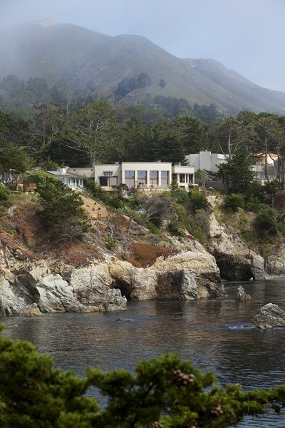 Modern home with outdoor, slope, trees, and shrubs. An amazing rugged ocean-side site Photo 2 of On the Edge