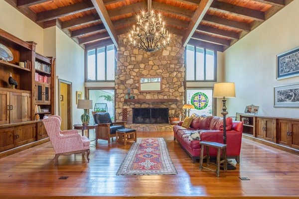 Living Room with soaring ceilings, heart pine floors, and built in cabinetry.  Wrought iron chandelier adds a rustic elegance. Photo 2 of Modernist MiniFarm in Cary NC modern home
