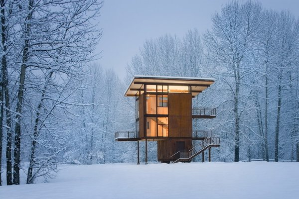 """Self-described by architect Olson Kundig Architects as """"basically a steel box on stilts,"""" the three-story cabin in upstate Washington can be completely sealed off to the elements with four 10' by 18' steel shutters that can be rolled over the glass windows when visitors clear out."""