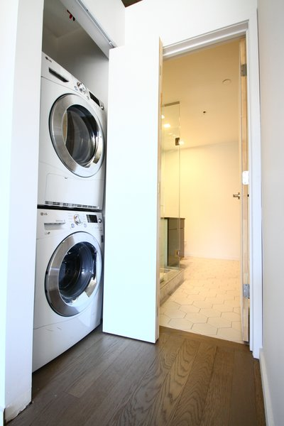 A stacked washer and ventless dryer fit in a closet with a bifold sliding door. Photo 8 of Silver Lining Loft modern home