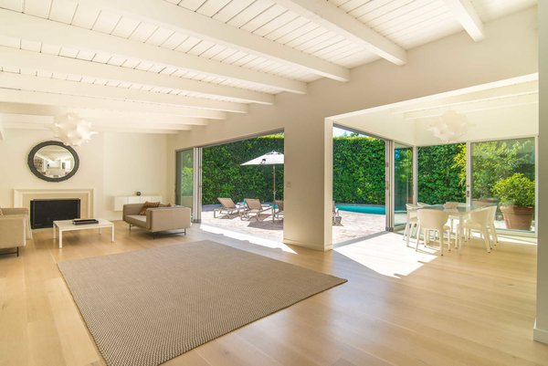 An open, light-filled living room with a fireplace and exposed beams is designed for embracing the quintessential California lifestyle, with sliding walls of glass to a fully-hedged swimming pool. Photo 2 of Nichols Canyon modern home