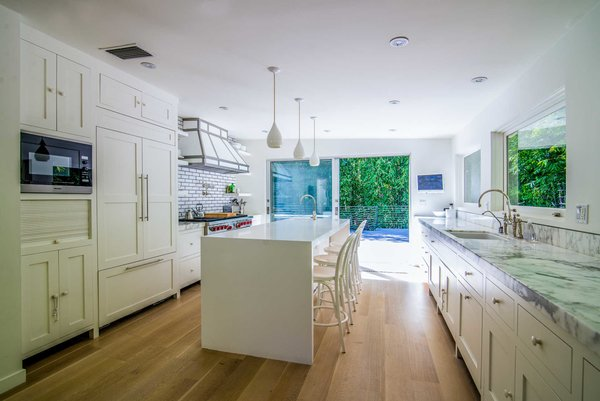 A spacious chef's kitchen features Calacatta marble countertops, Wolf and Miele appliances, a large eat-in island, and sliding walls of glass to an expansive rear deck for entertaining. Photo 3 of Nichols Canyon modern home