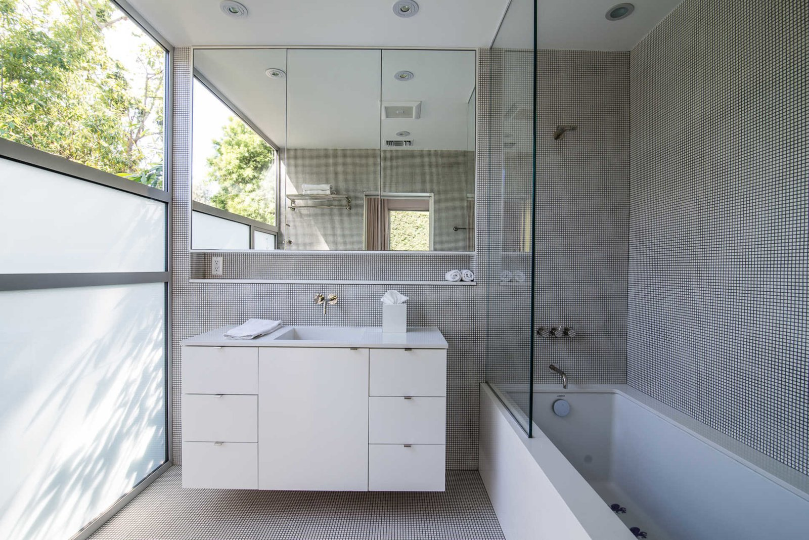 The home was thoughtfully designed to take full advantage of the property's idyllic surroundings. A serene guest bathroom features a frosted wall of glass and clerestory window, inspiring a gracious play on light and shadow. Nichols Canyon by Luxury Homes + Lifestyle