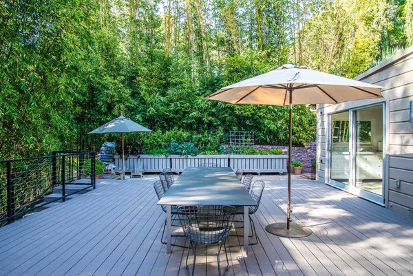 An expansive rear deck surrounded by lush bamboo hedges is a tranquil retreat for dining and lounging. Sliding pocket doors off the kitchen and bedrooms create a seamless connection with the outdoors. Photo 5 of Nichols Canyon modern home