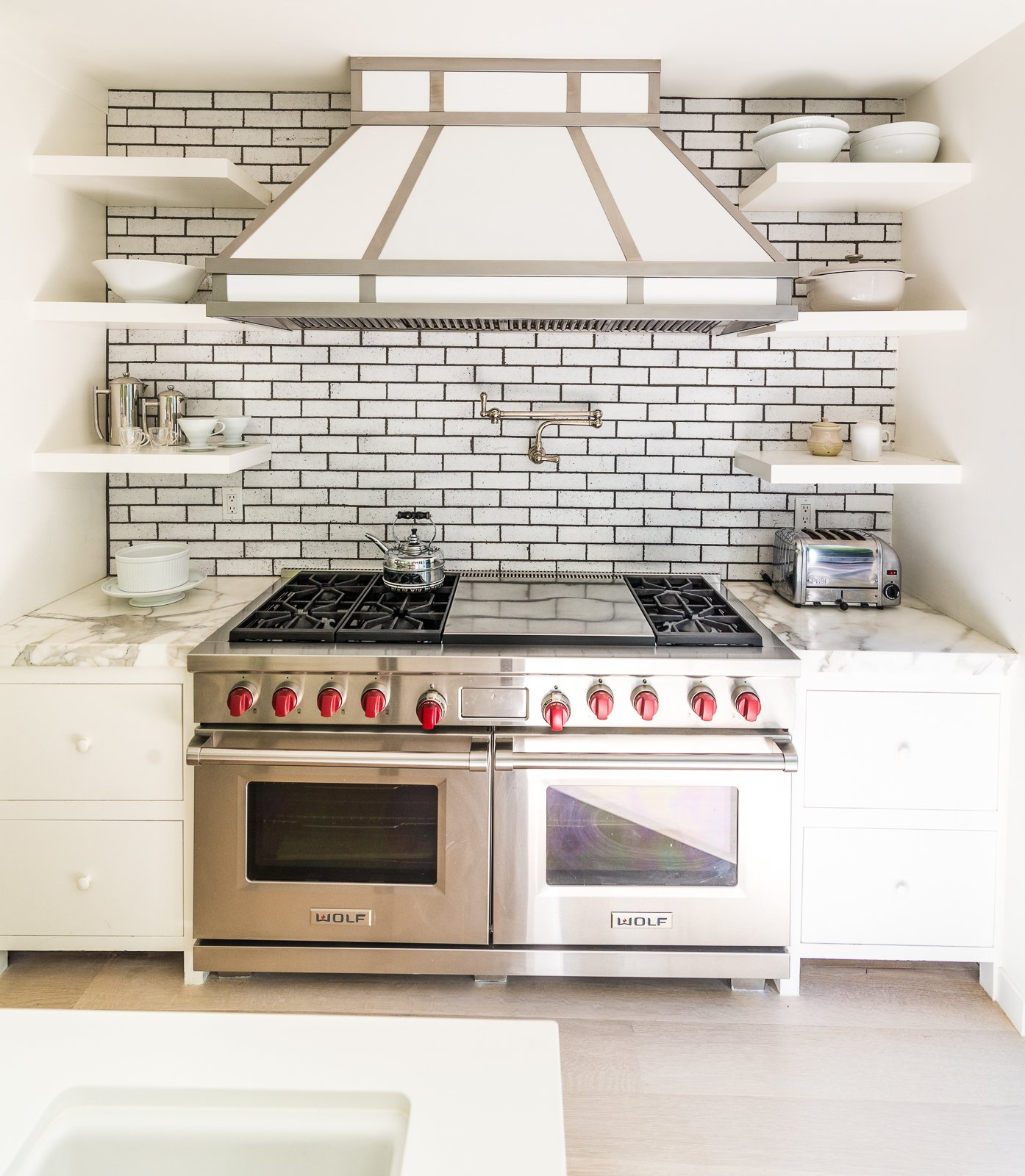 Calcutta marble adorns this beautiful stove top with dual oven and built in shelves  Nichols Canyon by Luxury Homes + Lifestyle