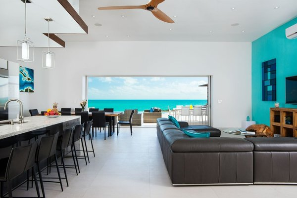 A 20-foot sliding wall of glass reveals incredible views of the turquoise waters and white sand beaches of Turks and Caicos.  Photo 4 of Tip of the Tail Villa modern home