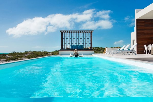 An incredible, glass-walled swimming pool overlooks the turquoise waters. Photo 7 of Tip of the Tail Villa modern home