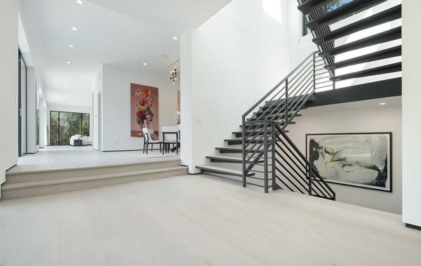 An airy foyer and light-filled corridor with sliding walls of glass and high ceilings that enhance the space and scale of every room. Photo 2 of Cherokee Contemporary modern home
