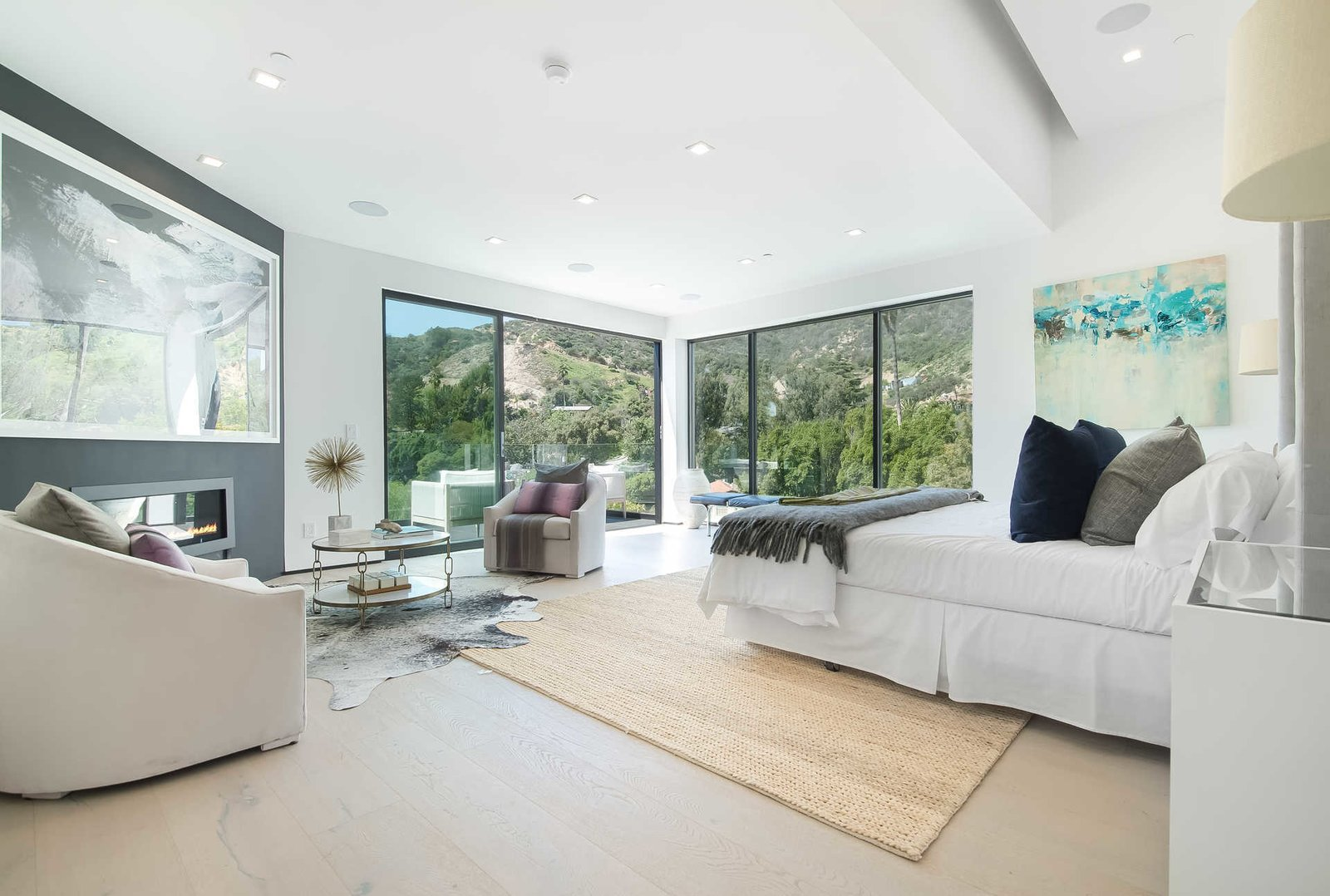 Walls of glass enhance the light and scale of the master suite.