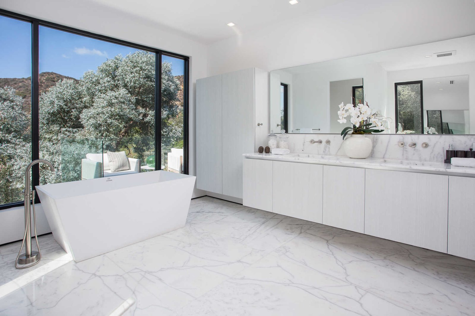An elegant bathroom with standalone tub overlooks the hills.  Cherokee Contemporary by Luxury Homes + Lifestyle