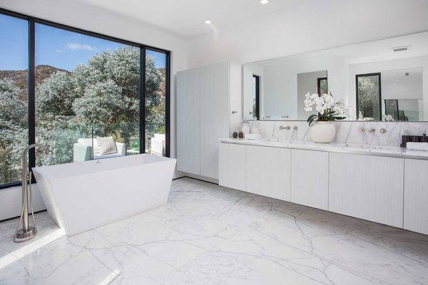 An elegant bathroom with standalone tub overlooks the hills. Photo 9 of Cherokee Contemporary modern home