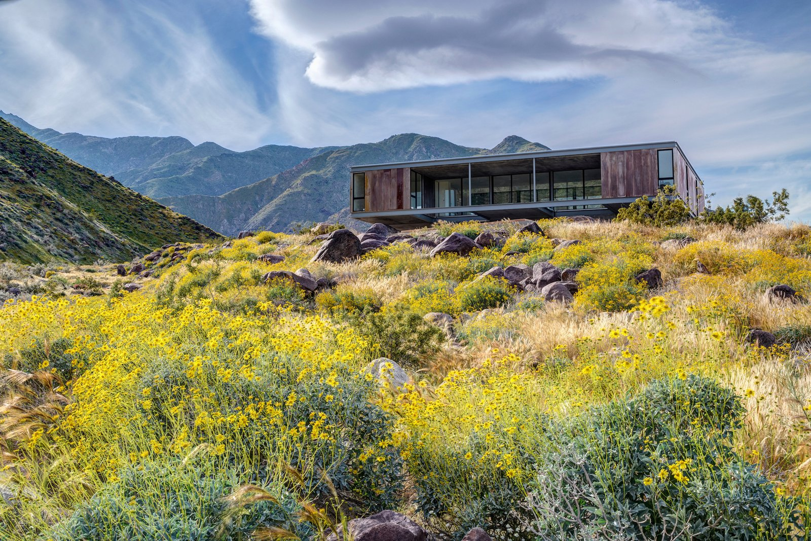 The Beadle House appears to float above the landscape, set upon a pedestal-like foundation. Desert Palisades Chino Canyon by Luxury Homes + Lifestyle