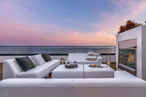 An outdoor gathering, dining and entertaining space with fireplace.  Photo 2 of Carbon Beach modern home