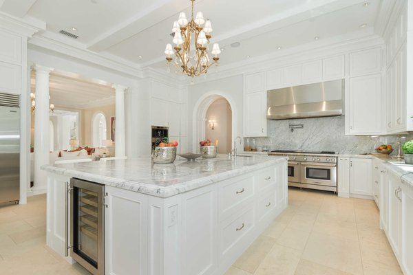 The magnificent chef's kitchen showcases custom cabinetry, stacked Wolf appliances, and a large eat-in island, with doors off the breakfast area offering a gracious flow to the gardens.  Photo 4 of Benedict Canyon Villa modern home