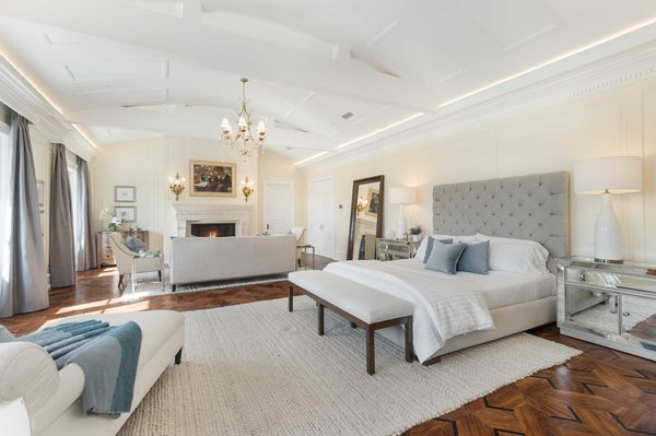 The 1700-square-foot master bedroom showcases inlaid walnut floors, a large fireplace, and French doors to a private terrace. Photo 5 of Benedict Canyon Villa modern home