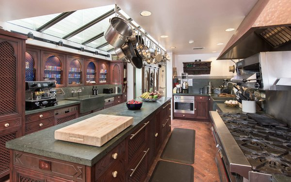 An expansive chef's kitchen with a farmhouse sink and large center island Photo 7 of Malibu Colony Road modern home