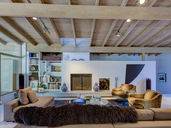 Smooth surfaces were favored over the home's original stone and wood, while built-in bookshelves add warmth to the space. Photo 5 of Midcentury Post and Beam In Fryman Canyon modern home