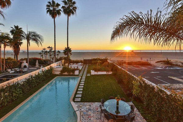 Modern home with back yard, large pool, large patio, porch, deck, tile patio, porch, deck, wood fence, and outdoor. A generous outdoor area boasts a large swimming pool and dining areas, with a gate opening directly onto the beach. Photo 2 of A Santa Monica Beach House Built for Norma Talmadge