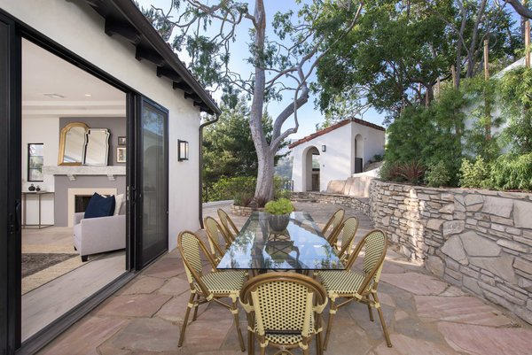Modern home with outdoor, side yard, trees, gardens, walkways, raised planters, and stone patio, porch, deck. An outdoor dining patio  off the living room embraces the quintessential California lifestyle. Photo 4 of A 1930s Spanish Colonial in Los Feliz Reimagined for the 21st Century