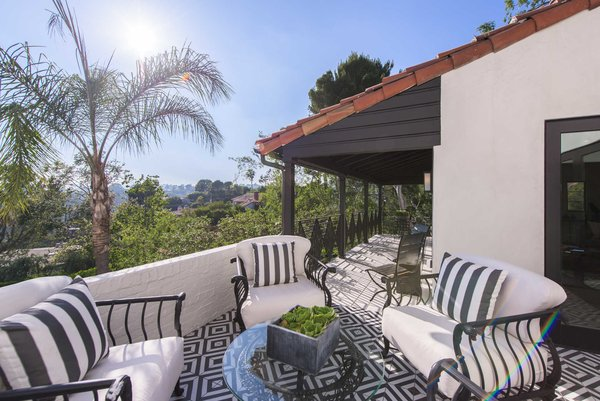 Modern home with outdoor, small patio, porch, deck, and tile patio, porch, deck. A tiled patio off an upstairs bedroom is a peaceful retreat, overlooking views of Hollywood and Century City all the way to the ocean. Photo 6 of A 1930s Spanish Colonial in Los Feliz Reimagined for the 21st Century