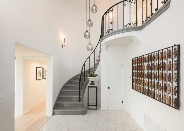 Modern home with staircase, stone tread, and metal railing. The home's original magnesite staircase leads to the perfect family floor plan. Photo 9 of A 1930s Spanish Colonial in Los Feliz Reimagined for the 21st Century