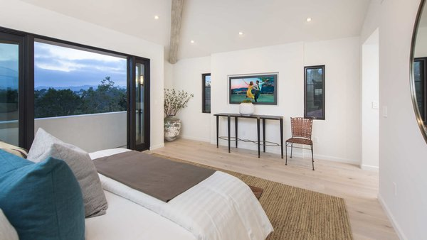 Modern home with bedroom, bed, recessed lighting, chair, and light hardwood floor. A voluminous master suite features vaulted ceilings, dual showroom closets and sliding pocket doors to a large terrace. Photo 10 of A 1930s Spanish Colonial in Los Feliz Reimagined for the 21st Century