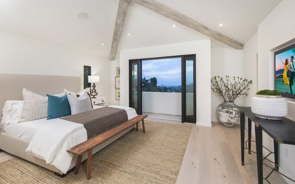 Modern home with bedroom, bed, bench, light hardwood floor, recessed lighting, and night stands. Photo 11 of A 1930s Spanish Colonial in Los Feliz Reimagined for the 21st Century