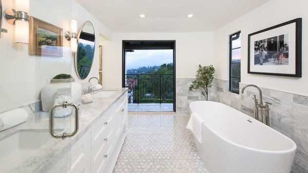 Modern home with bath room, marble counter, enclosed shower, drop in sink, recessed lighting, marble wall, wall lighting, freestanding tub, and one piece toilet. A soaking tub in the master bathroom, with doors to the observation terrace. Photo 12 of A 1930s Spanish Colonial in Los Feliz Reimagined for the 21st Century
