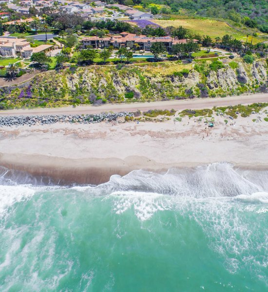 Modern home with outdoor, trees, shrubs, grass, swimming pool, back yard, gardens, and walkways. Showcasing 450 feet of ocean frontage, the residence offers elevated views of the sweeping coastline. Photo  of A Monumental Oceanfront Estate on the California Coast