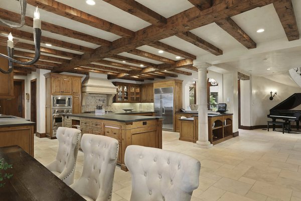 Modern home with kitchen, wood cabinet, stone tile backsplashe, recessed lighting, wall lighting, refrigerator, microwave, wall oven, cooktops, range, range hood, and drop in sink. A staggering chef's kitchen is heightened by exposed wood beams and limestone floors. Photo 4 of A Monumental Oceanfront Estate on the California Coast