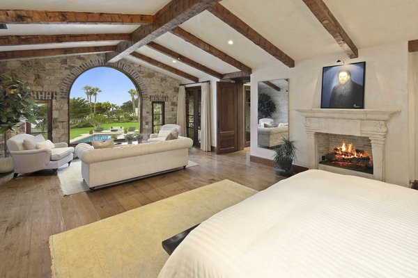 Modern home with bedroom, bed, recessed lighting, medium hardwood floor, and chair. An impressive master suite boasts wide plank hardwood floors, exposed beams and dramatic windows overlooking the pool and expansive grounds. Photo 7 of A Monumental Oceanfront Estate on the California Coast