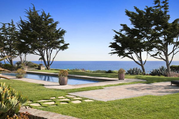 Modern home with outdoor, trees, grass, back yard, gardens, walkways, hardscapes, large pool, and swimming pool. Photo 10 of A Monumental Oceanfront Estate on the California Coast