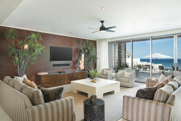 Modern home with living room. The great room with dark-hued accent wall and receding glass doors.  Photo 3 of A Contemporary Makeover Transforms Oceanfront Villa Serena