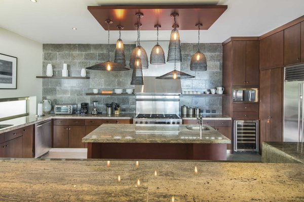 Modern home with kitchen, granite counter, stone tile backsplashe, and pendant lighting. The gourmet kitchen with large, center prep island, stone backsplash and pendant lighting. Photo 4 of A Contemporary Makeover Transforms Oceanfront Villa Serena