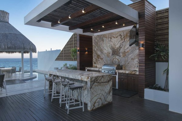 Modern home with outdoor. Marble and wood poolside cooking area with casual, countertop seating.  Photo 5 of A Contemporary Makeover Transforms Oceanfront Villa Serena