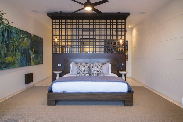 Modern home with bedroom and bed. Master bedroom suite with gallery walls and rich wood accents.  Photo 6 of A Contemporary Makeover Transforms Oceanfront Villa Serena