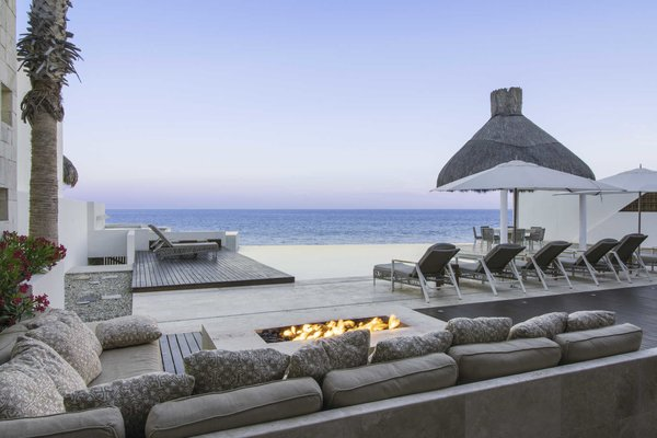 Modern home with outdoor. The limestone fire pit and pool terrace at twilight.  Photo 7 of A Contemporary Makeover Transforms Oceanfront Villa Serena