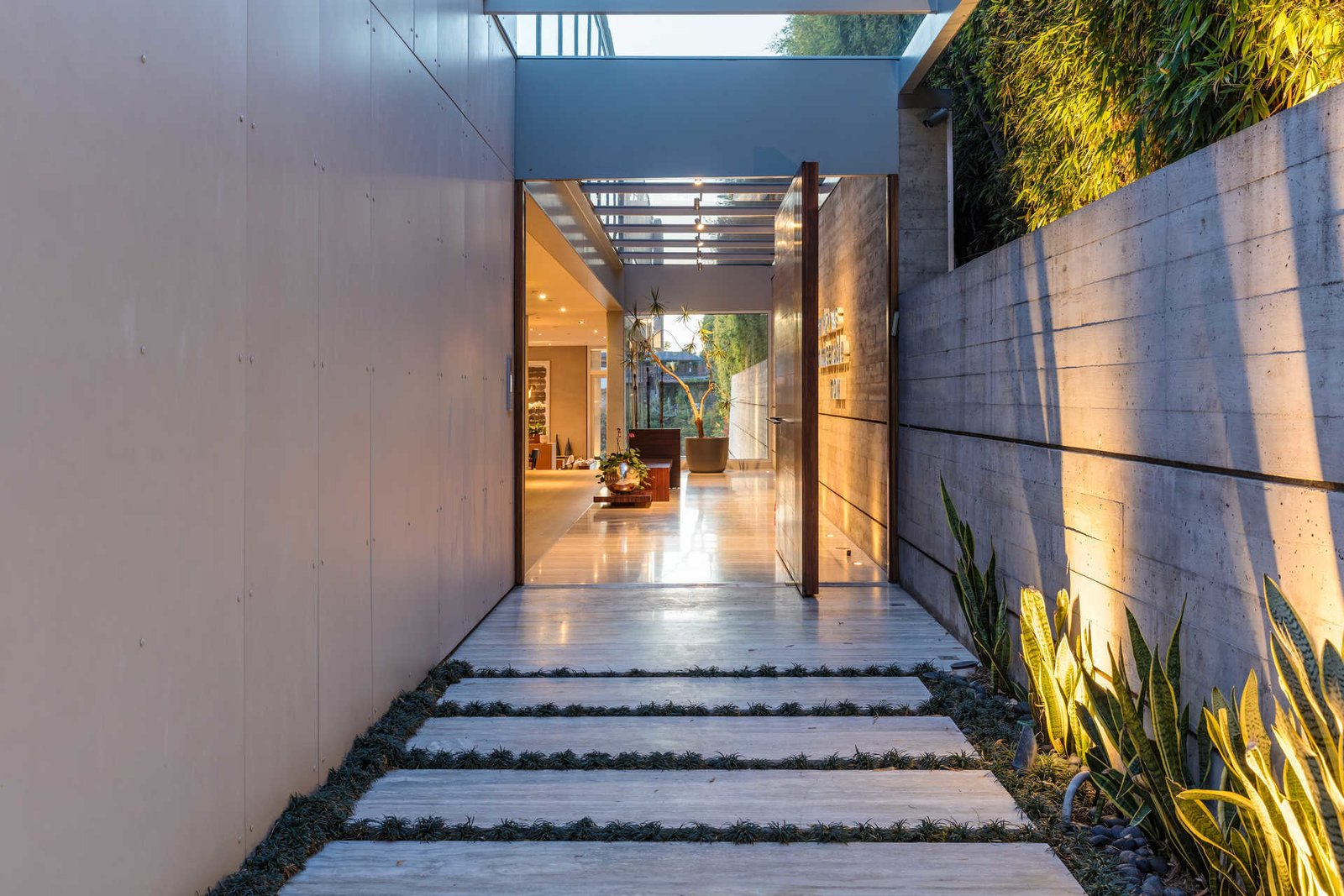 A tranquil meditation garden leads to a light-filled entrance gallery punctuated by a glass-paneled ceiling.