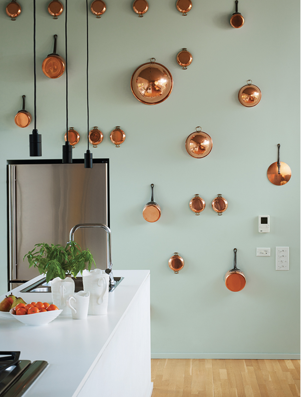 A wall of artfully arranged copper pots with a contrasting paint color makes a bold statement in a small space.
