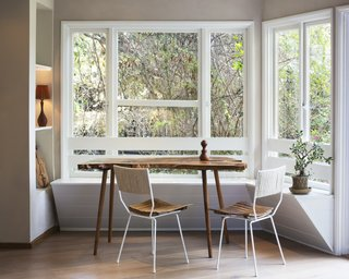 A beautifully simple shiplap built-in banquette balances perfectly with a live edge table, making the most of the abundant natural light.