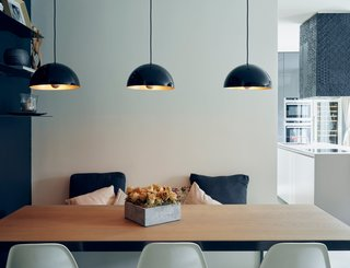 5 Main Ingredients For Cooking Up a Homey Kitchen Nook - Photo 2 of 8 - Three simple light fixtures with a pretty brass finish add a warm glow to a cool-toned room.