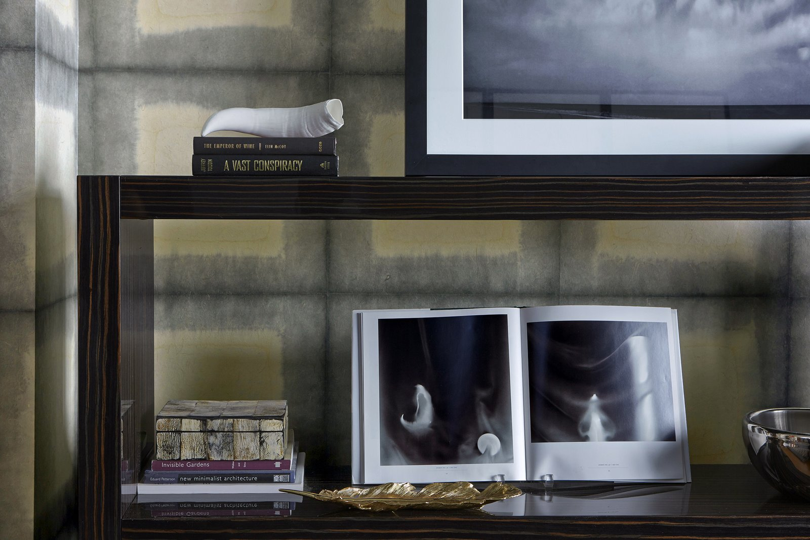 A rosewood Italian console from Minotti contrasts with handmade indigo Japanese wallpaper from Larsen. This beautiful shelving offers an area to display the client's books and vintage items.  Bachelor Pad by Jarret Yoshida Inc.