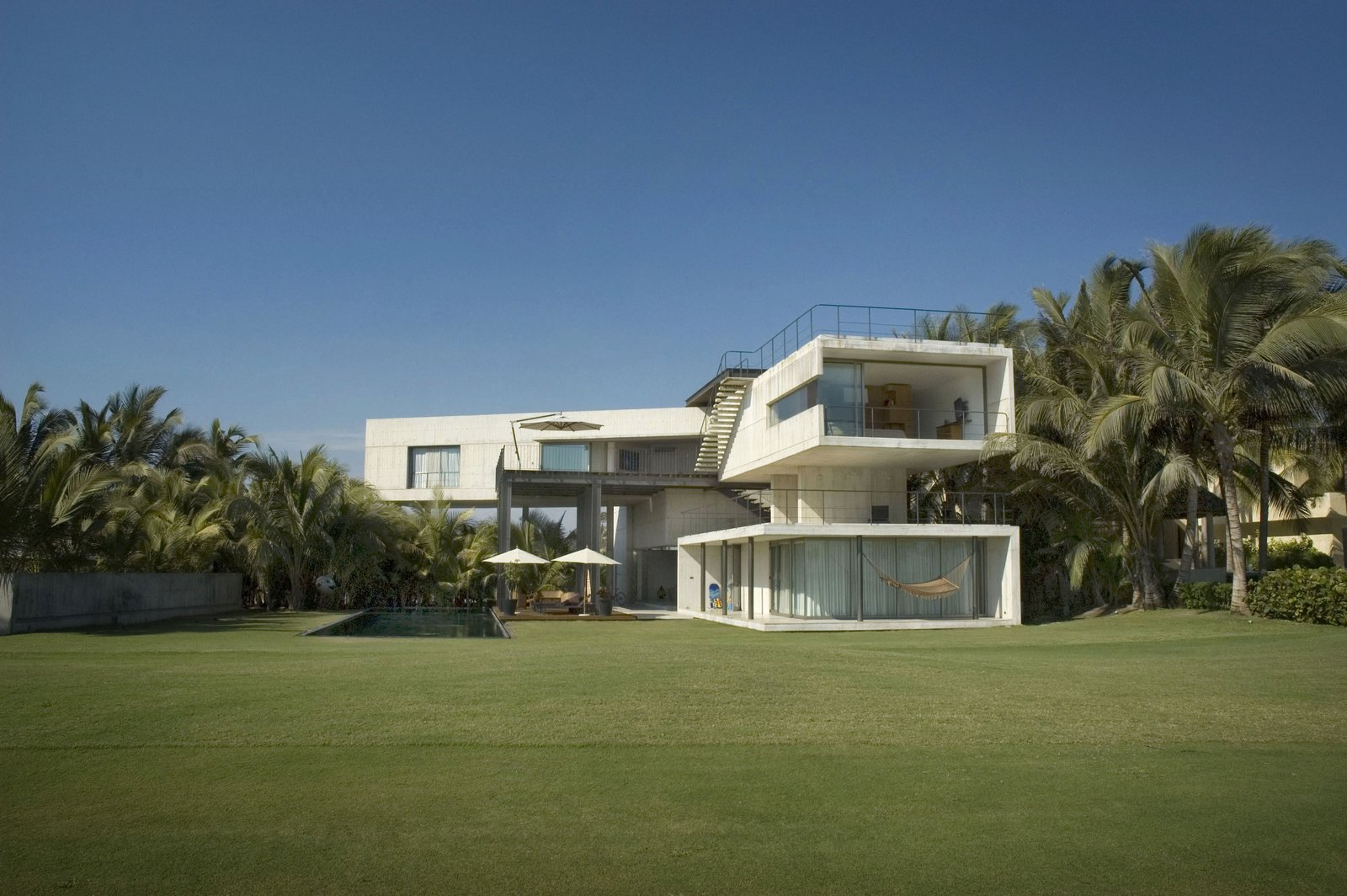 View from the Gulf Course to the House Tagged: Outdoor, Garden, Grass, and Concrete Patio, Porch, Deck.  La Caracola Beach House by PAUL CREMOUX studio