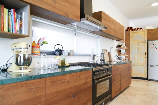 Modern home with kitchen, wood cabinet, limestone floor, ceiling lighting, and stone counter. The kitchen Photo 15 of A house in the mountains