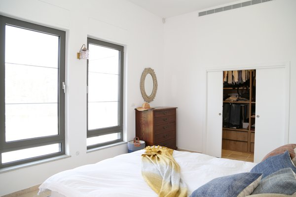 Modern home with bedroom, bed, wall lighting, and travertine floor. Master bedroom Photo 3 of A house in the mountains