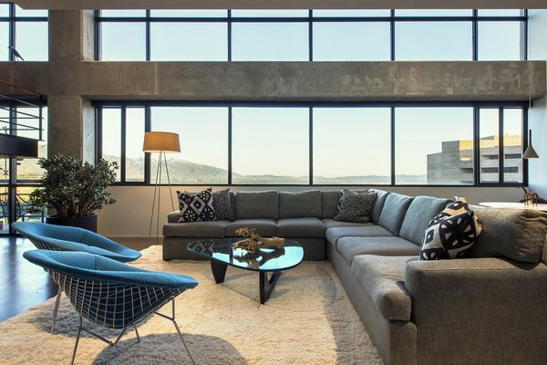 Modern home with living room, coffee tables, chair, floor lighting, sectional, and concrete floor. living room - looking to wasatch mountains and salt lake city beyond Photo  of Governors Plaza