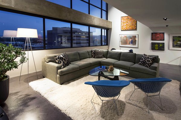 Modern home with living room, sectional, floor lighting, chair, recessed lighting, coffee tables, and concrete floor. living room - looking west at dusk Photo 2 of Governors Plaza